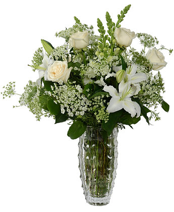 Jubilee of white lilies roses snapdragon and Queen Anne's Lace and arranged it in an elegant cut glass vase