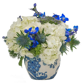Hydrangea Ranunculus and Delphinium with Thistle and Trachelium in a Delft globe container