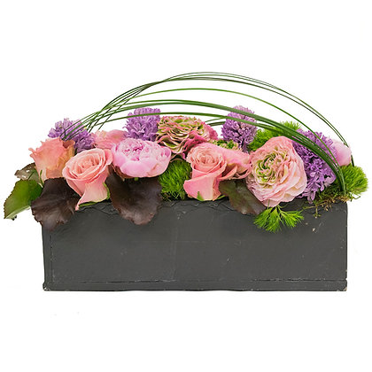 Peonies Ranunculus Roses Hyacinth and Dianthus in a faux rectangle slate container with galax leaves moss and steel grass