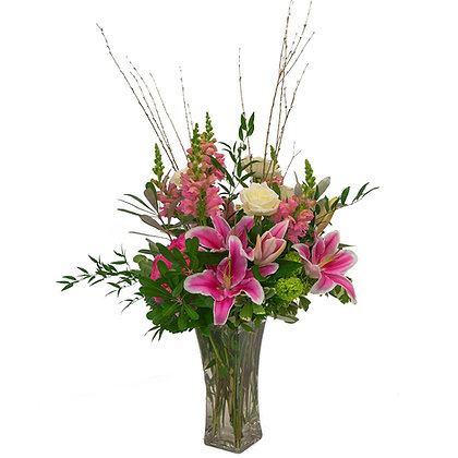 Hydrangeas snapdragons roses hybrid lilies and viburnum in a tall Marquise glass vase with ruscus pittosporum integrifolia