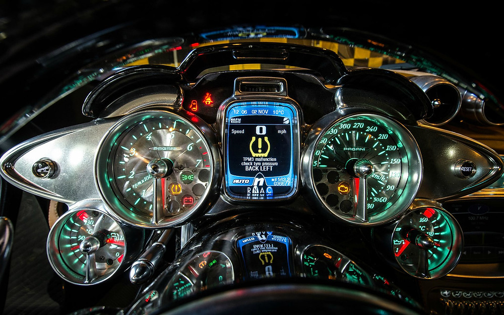 Instrument panel of a late model Pagani Huayra lit in green.