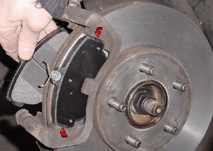 A brake disc with outboard pad in place and inboard pad in the mechanic's hand.
