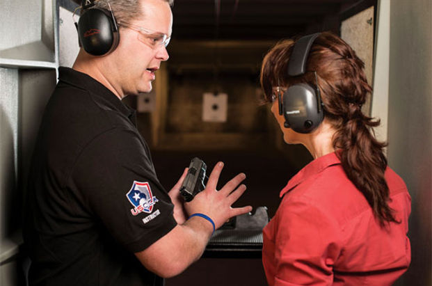 Male USCCA Instructor teaching pistol fundamentals to female student at CT shooting range