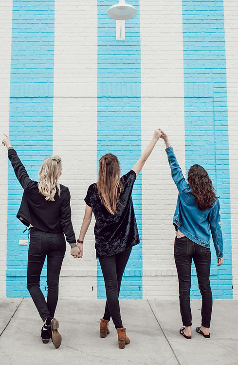 Three women holding hands, facing a blue and white striped brick wall.