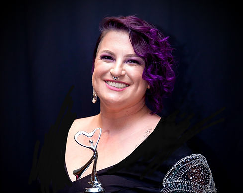 Mel with curly purple hair, wearing a black dress, smiling while holding a silver trophy.