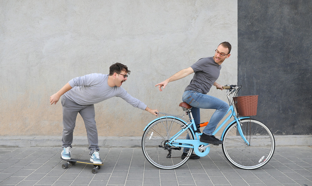 one man on skateboard and one man on bicycle