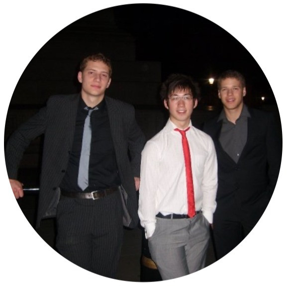 Image of three men in suits posing for photo