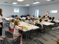 Students sitting at tables learning in a classroom.