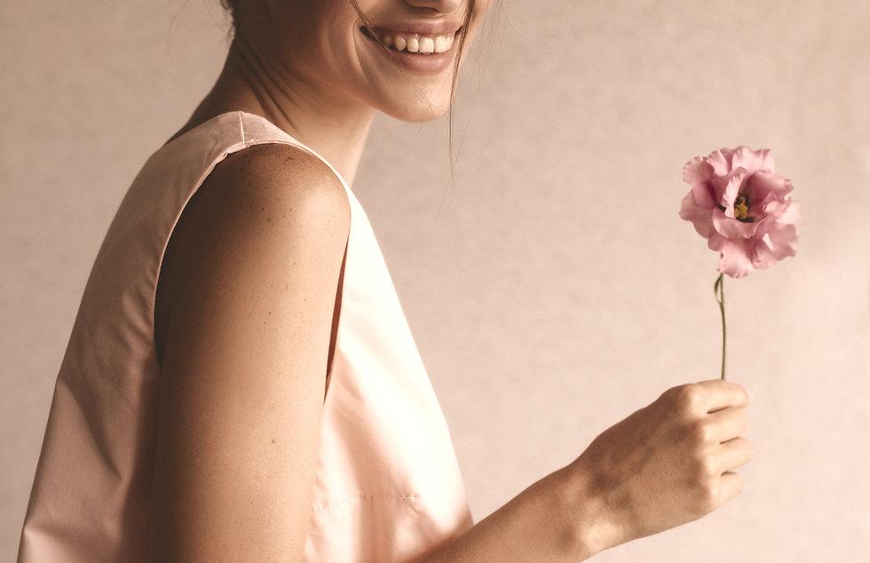 Femme qui tient une fleur