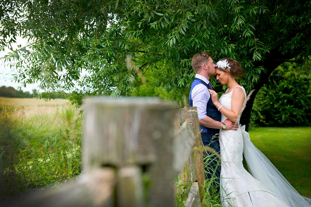 Newly wed couple pictured in a meadow