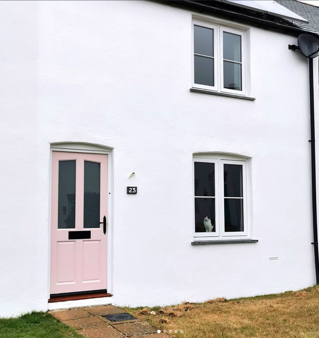 White painted house with pink door