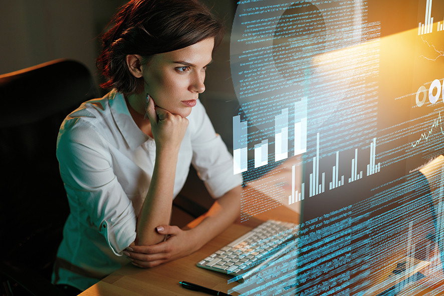 Image of woman viewing lots of data on screens