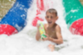 Boy sliding throughh foam spraying Fozzi's Foam Spray