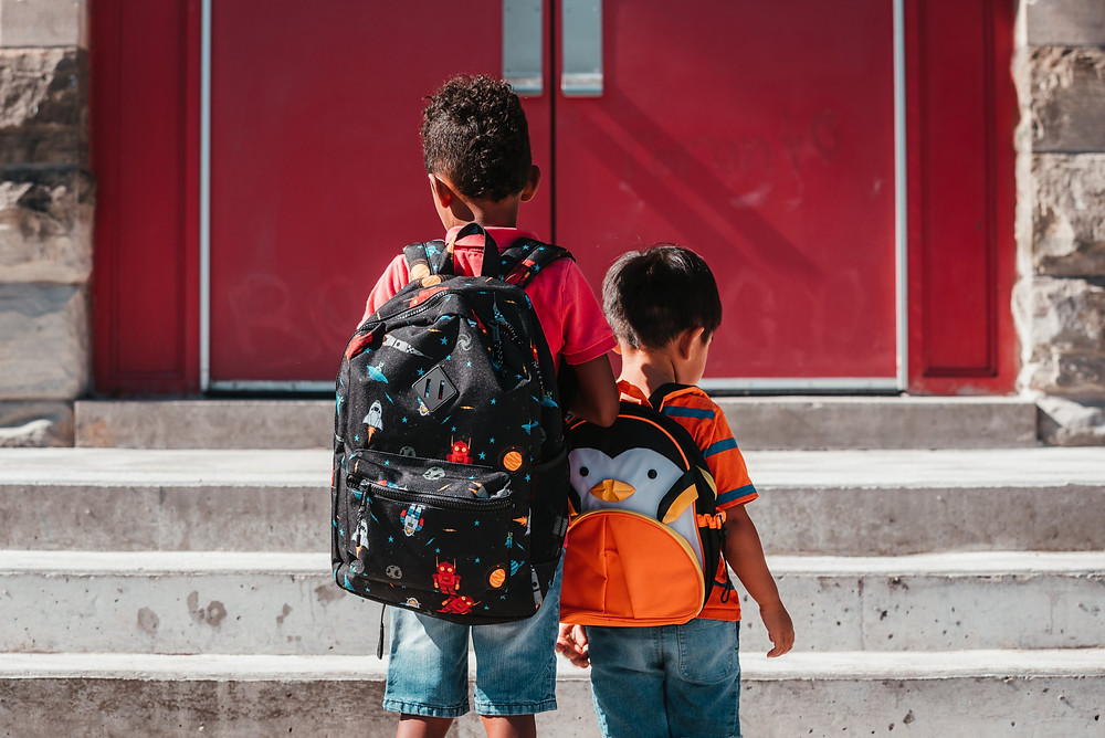 Two young boys carrying backpacks walking up steps into school.