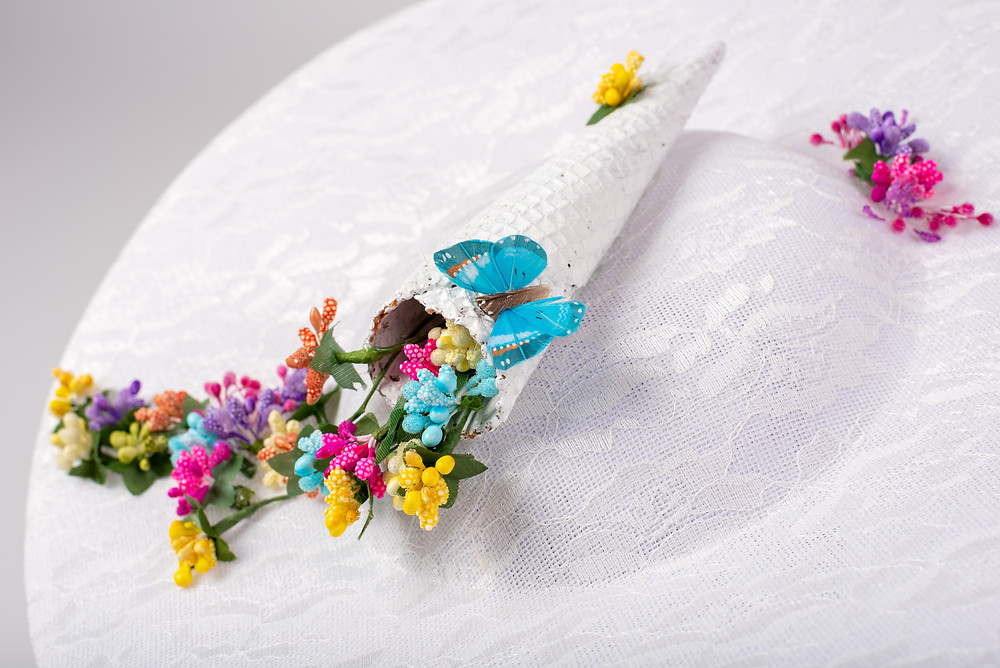 A lovely white Brocade Hat, with dainty flowers cascading from an Ice-Cream Cone, and a Butterfly hovering!