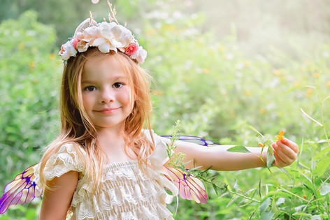 A female child poses in a sundress, flower crown and fairy wings at Beechwood Farms Nature Reserve in Fox Chapel, Pennsylvania.