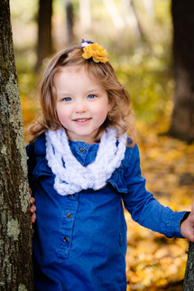 A little girl in Moon Township Community Park, smiling by a tree with golden autumn leaves around her.