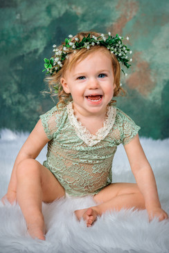 Studio portrait of a smiling toddler girl with blue eyes and curls, wearing a green lace romper and a flower crown.