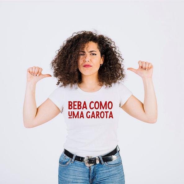 """Mulher usando uma camiseta branca escrita """"Beba Como Uma Garota""""."""