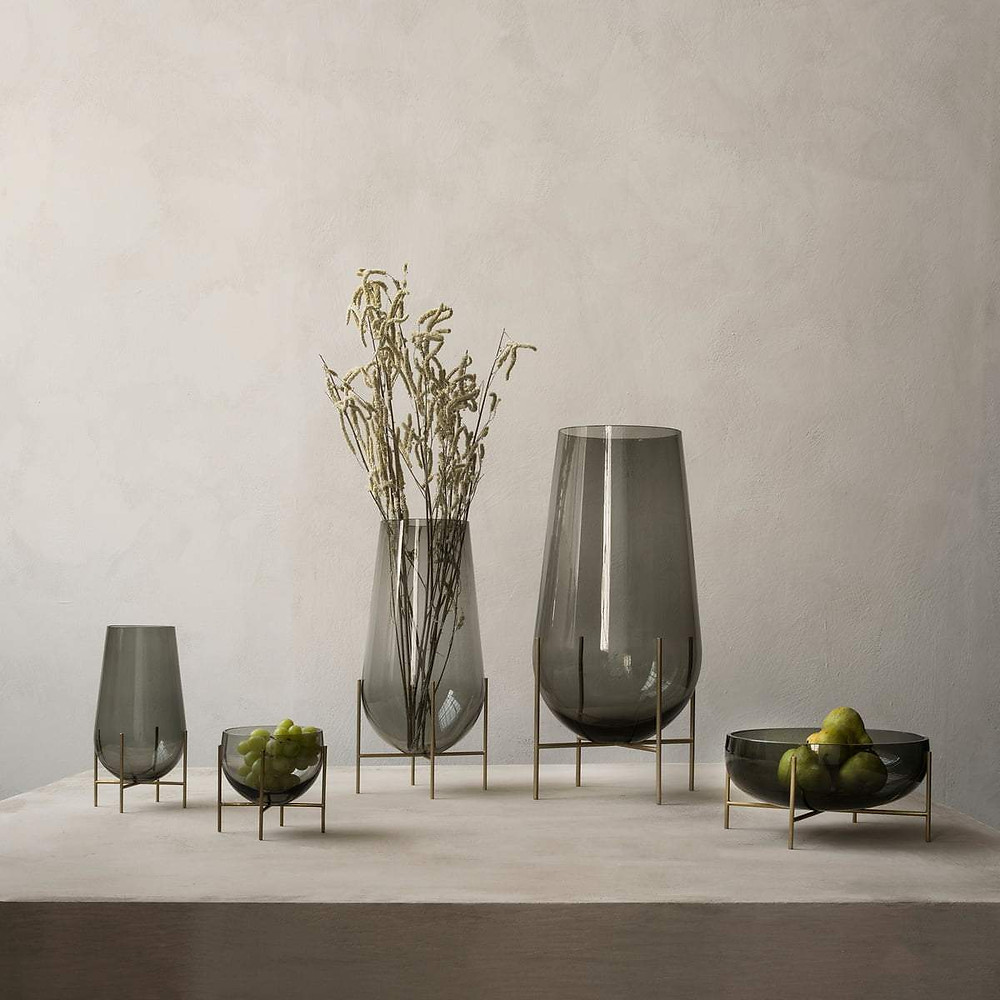 This stunning floor standing vase, designed for Danish brand Menu by rising star Theresa Arns, combines the classic elegance of a traditional vase with the playful addition of an anchoring table of four slender brass legs that resemble stilts. The word echasse is French for stilts. The coloured, graduated smoked glass, together with the brass legs creates a unique expression.
