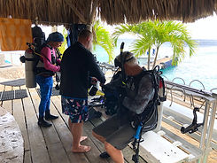 three people gearing up to go scuba diving
