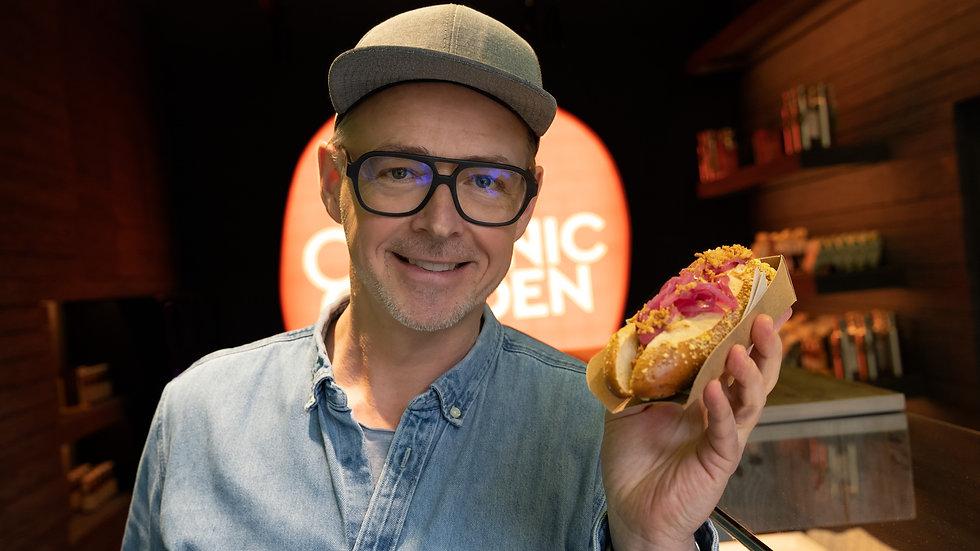 Holger Stromberg im Organic Garden Signature, hält einen veganen Hotdog in die Kamera