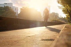 Canva - woman walking exercise on the road in the park, sunset background.jpg