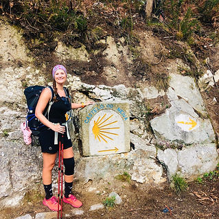 Sarah stood next to the Camino sign on the Camino Portuguese.