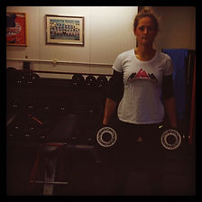 Sarah wearing a tough girl challenges t-shirt, while lifting weights