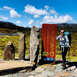 Sarah stood by the Overland Track sign, wearing a blue & white checked shirt & green Osprey backpack