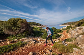 Sarah walking on the Lycian Way, Turkey. Blue skies, dirt track, striding along with purpose.