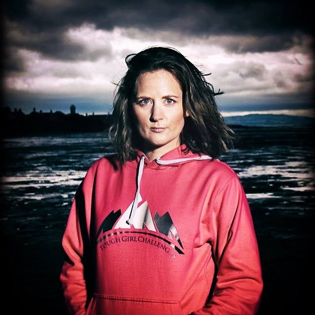 Sarah is wearing a pink tough girl hoody on the beach, with an intense look on her face.