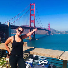 Sarah is stood with her bike in front of the Golden Gate Bridge in San Fransisco.