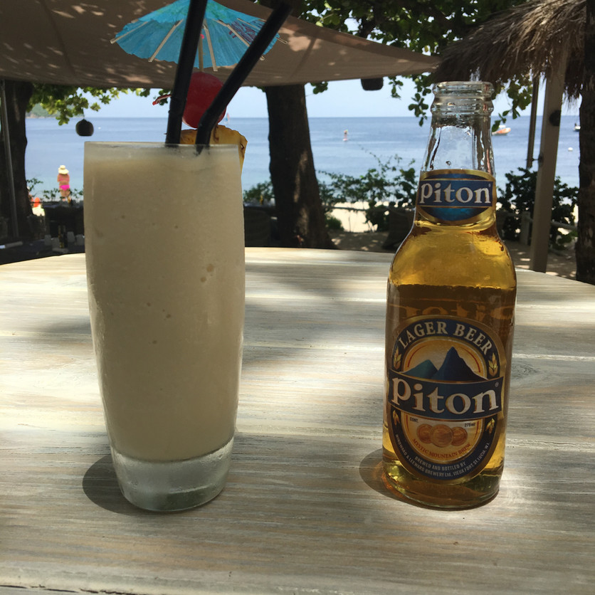 A Piña Colada & Piton Beer at the beach bar. Pitons Bay in the background.