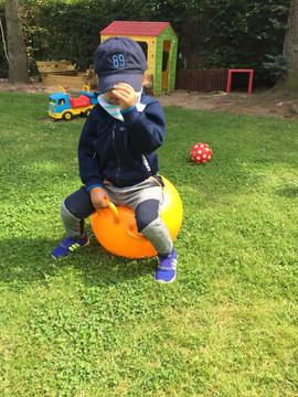Junge spielt mit Hüpfball im Garten