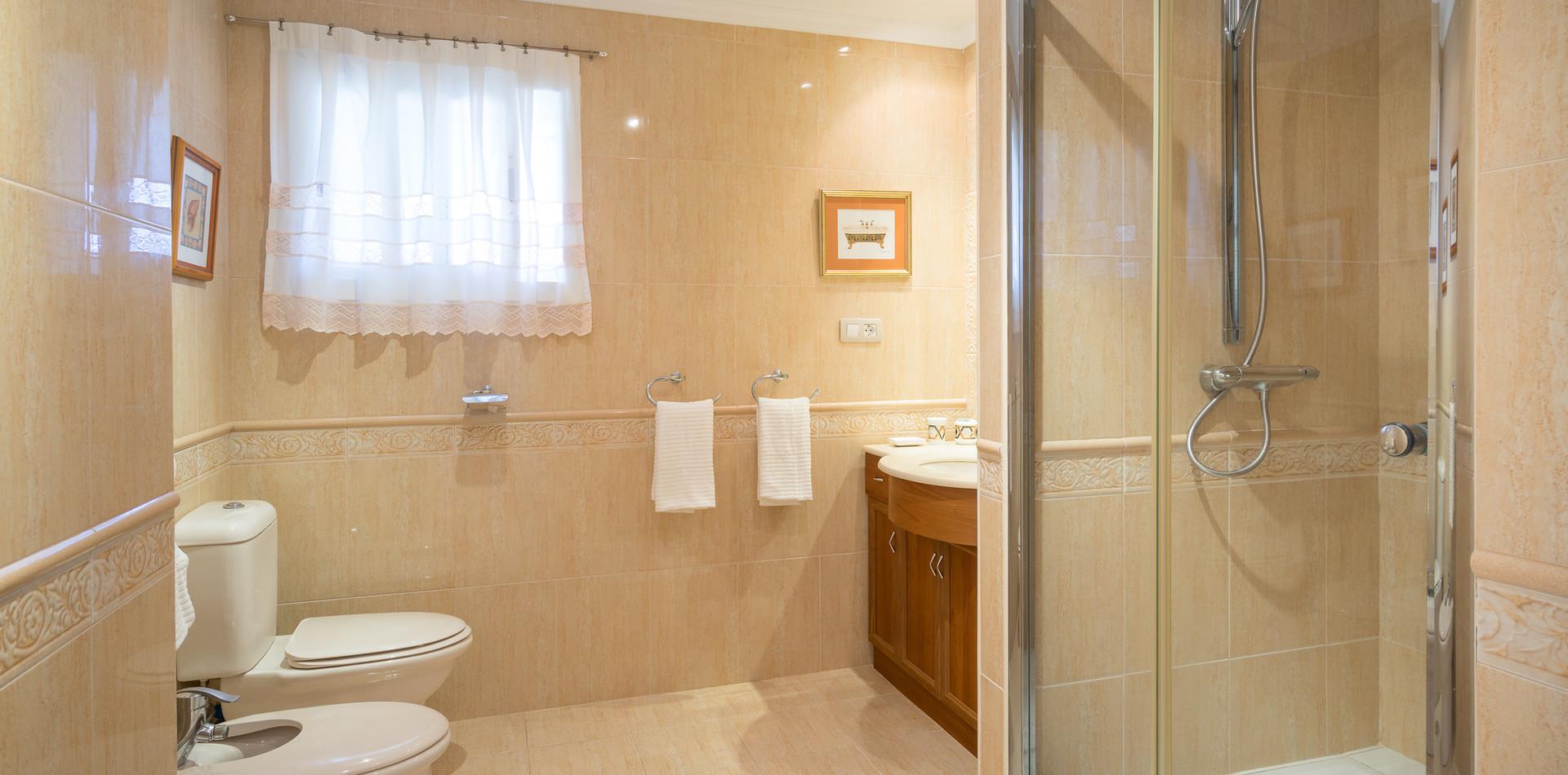 Baño completo con bañera y ducha, más cuarto de baño separado.