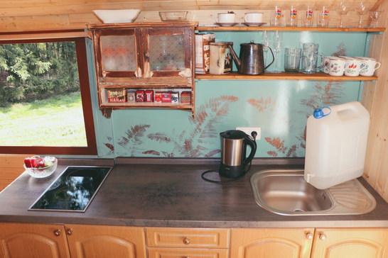 Součástí kuchyně je varná deska, rychlovarná konvice a teď už máme nové i tekoucí studenou i teplou vodu na dřezu.