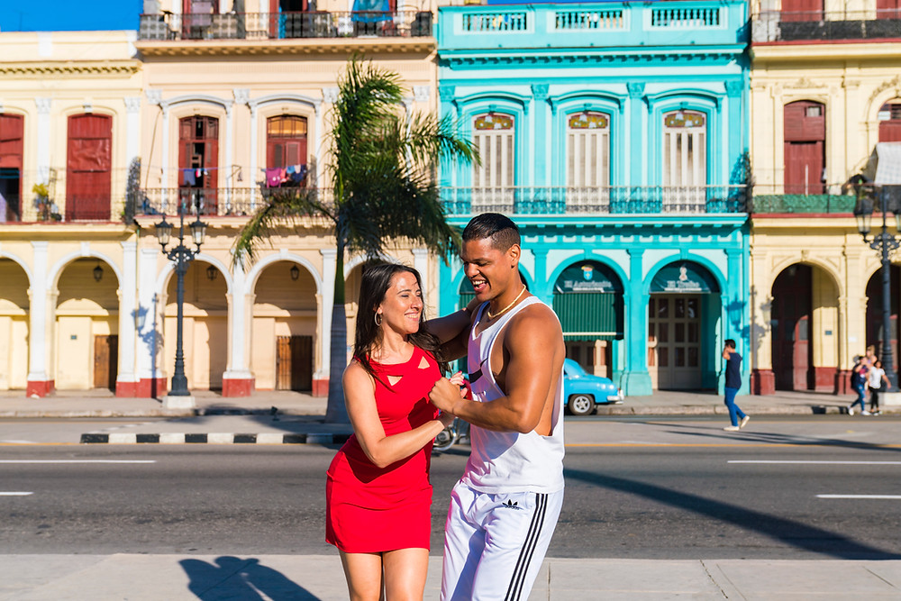 Melissa Mansfield in a bright red dress dances with a male Cuban dancer on the sidewalk in front of colorful buildings in Havana, Cuba
