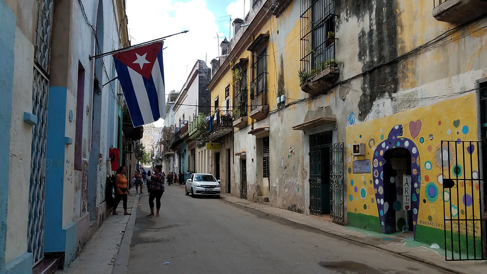Street in Havana Vieja in Cuba with Cuban flag