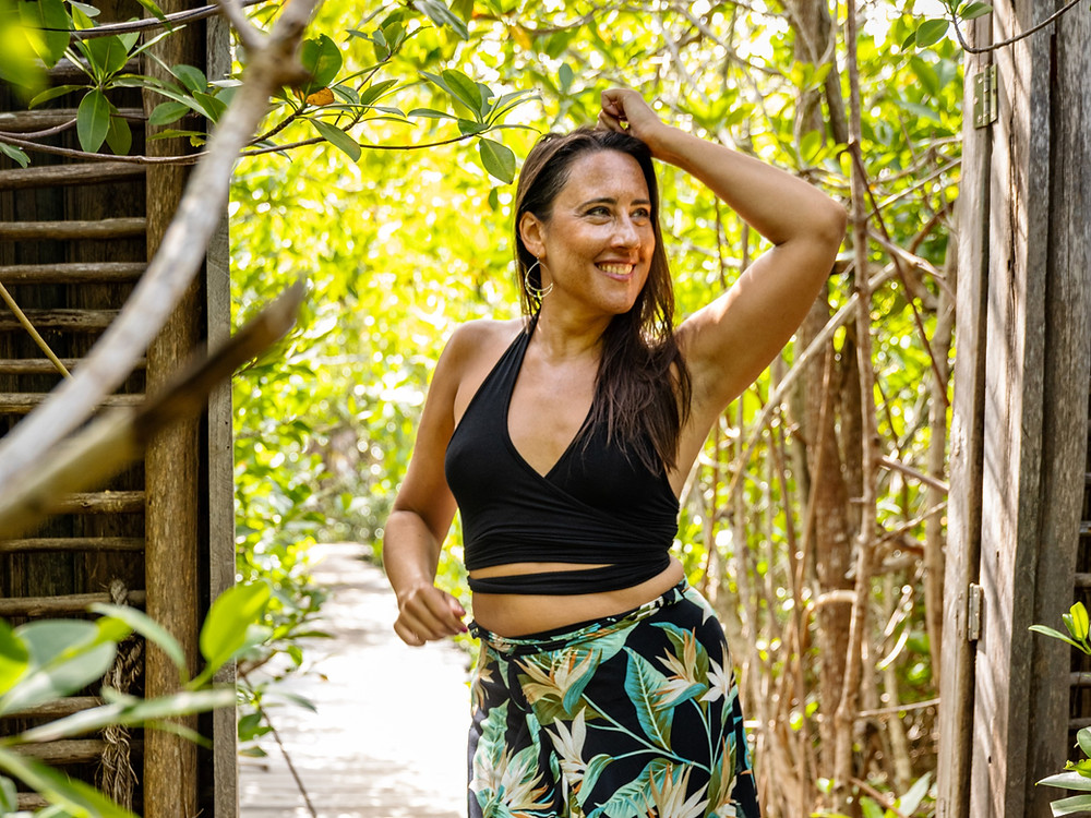 Melissa is dancing, smiling and looking over her left shoulder, with a natural background filled with sunlight and trees.