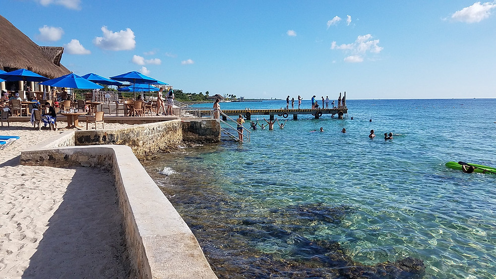 Sandy beach with tables and blue umbrellas border torquoise water of Cozumel with several swimmers