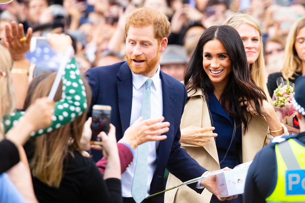 Duchess and Duke of Sussex smiling at crowd