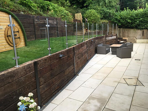 Very steep hillside garden, terraced lawn with glass bulstrade and Italian porcelain patio area.  Sleeper wall retainer and gravel drainaway.  New fencing