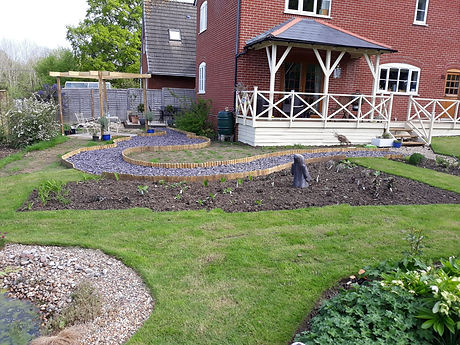 Garden regeneration project with gravel pathways, new flower beds, a ponde and new turf laid.  A gazebo has been installed over a paved area as a dining patio.  Edging was laid using log rolls.