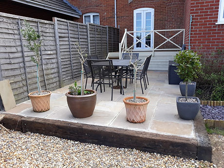 Simple Patio built using reclaimed oak railway sleepers as an edging.  The sleepers won't rot.  Paving is indian sandstone, but we sometimes lay porcelain tiles for a touch of real luxury and high end finishing for landscaping and garden projects