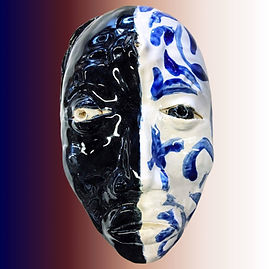 Ceramic mask of a human face, painted half black on left and white with blue splotches on right