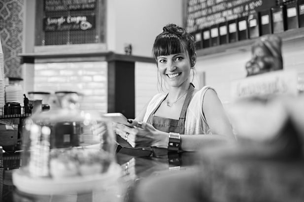Barista behind counter with phone in hand, looking at the camera and smiling