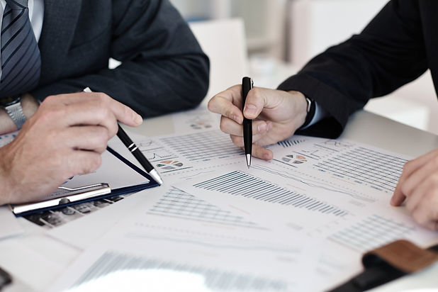 Two people sitting over a desk and looking over charts and graphs, pen in hands