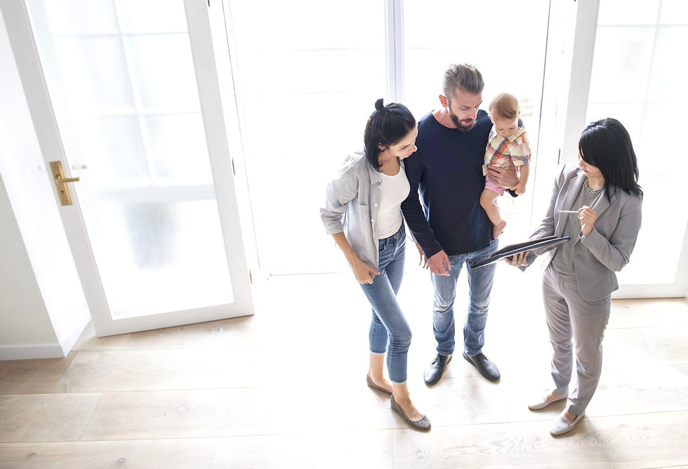 Image of a real estate agent showing her plans to a family of three- two parents and one infant