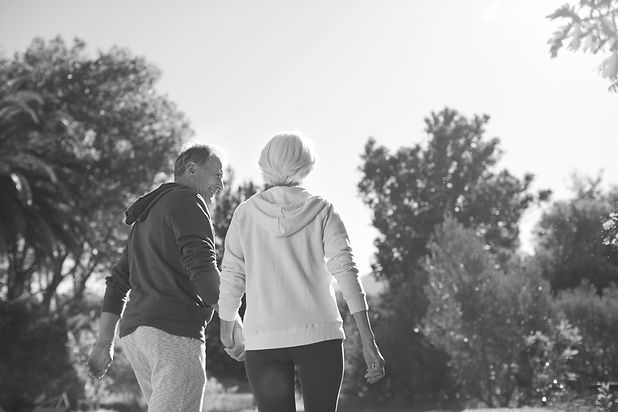 A couple dressed in athleisure clothes, an older man and woman, holding hands and walking together